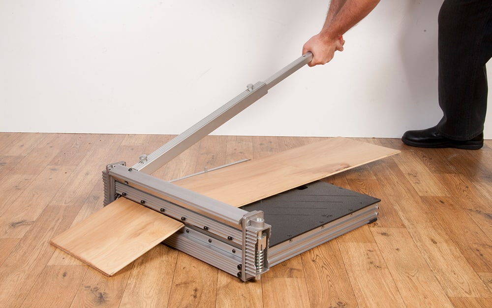 A person uses a vinyl cutter to trim a luxury vinyl plank.