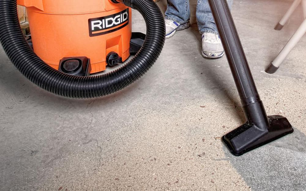 A person uses a vacuum to clean a concrete floor.