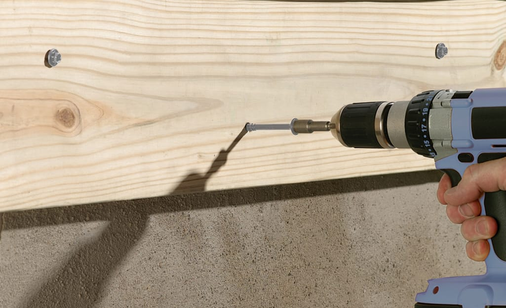 A person uses a drill to install screws.