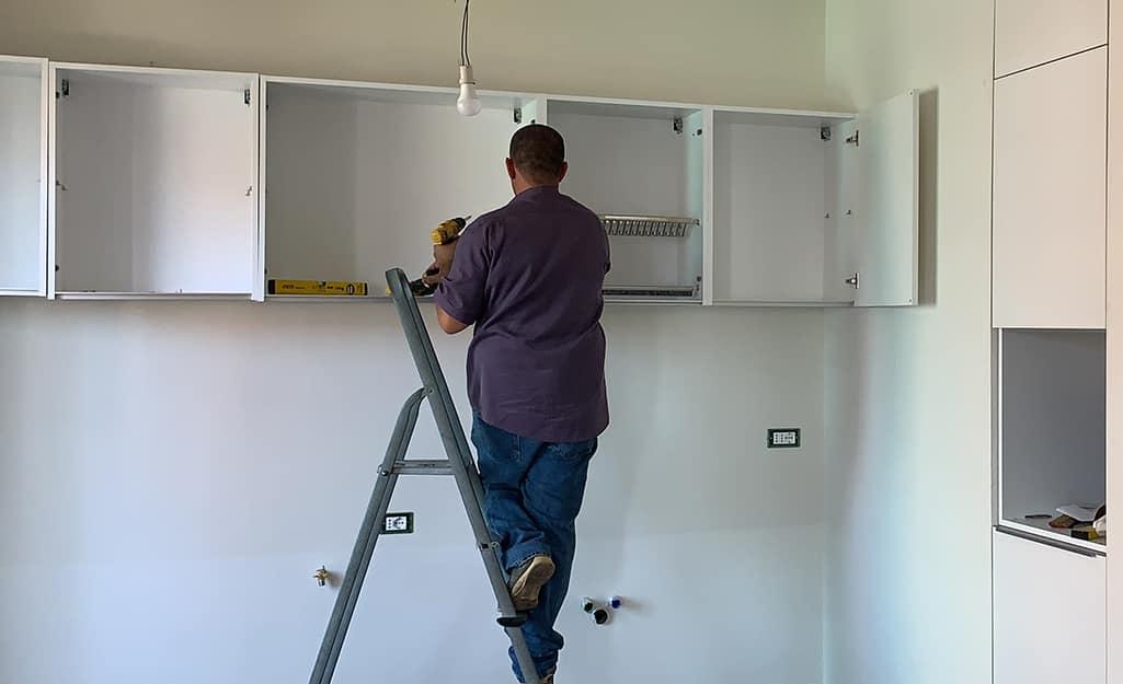 A person hangs upper cabinets.