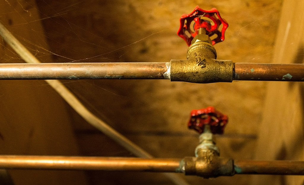 Main water supply shut-off valves on copper pipe in a basement.