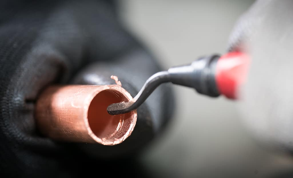 A person using a deburring tool to remove burrs from a cut copper pipe.