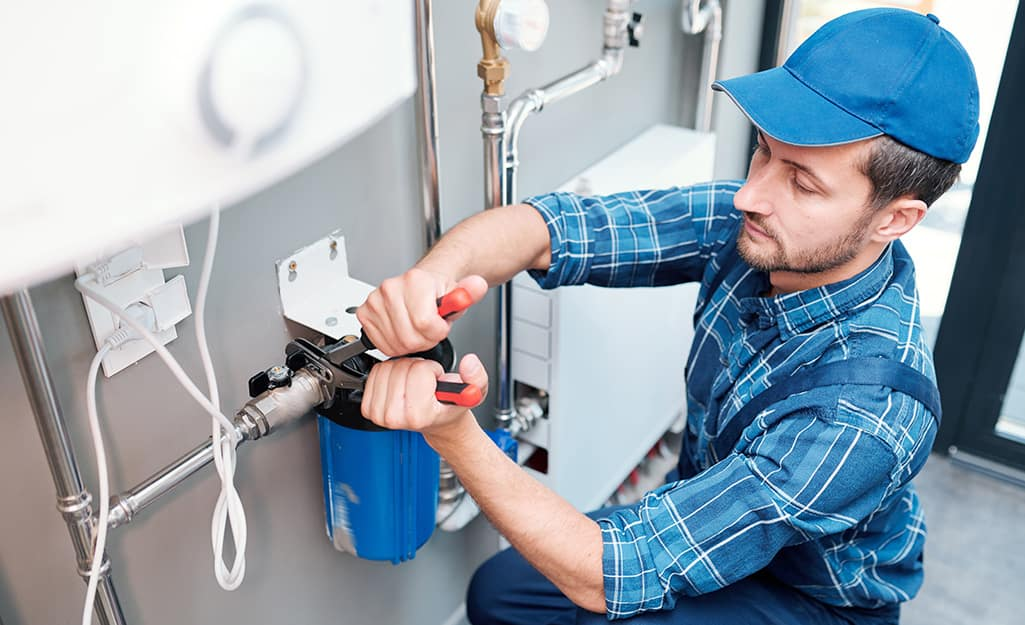 A person installing a shut-off valve to whole house water filter.