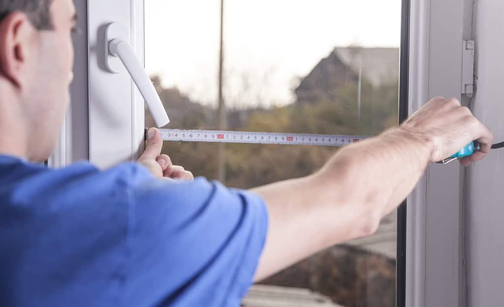 A man measuring a window.