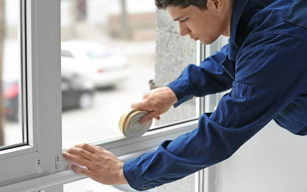 A man adding weather stripping to window.