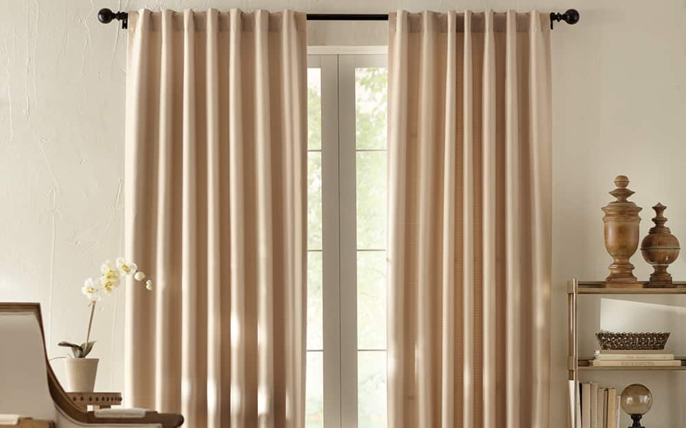 Long thermal window curtains hanging in a room.