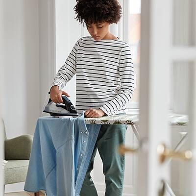 A woman ironing a shirt.