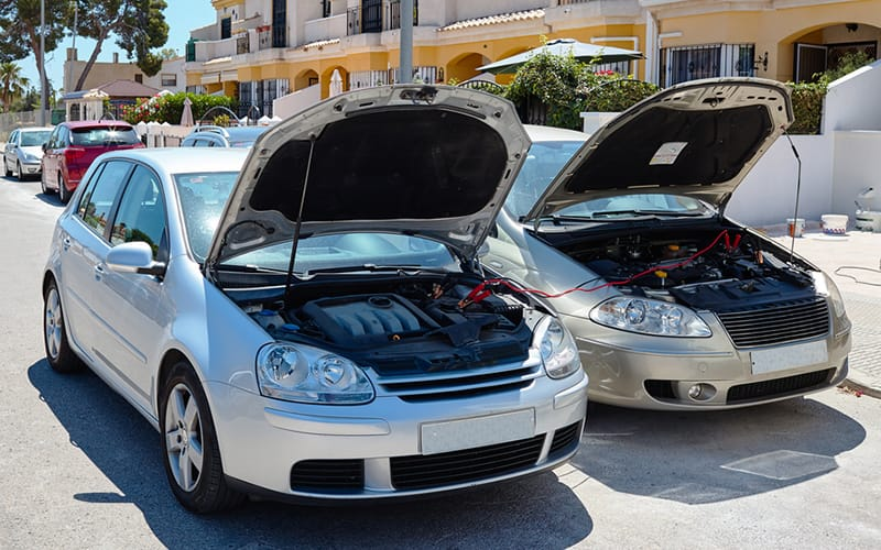 two cars side by side with each front hood open