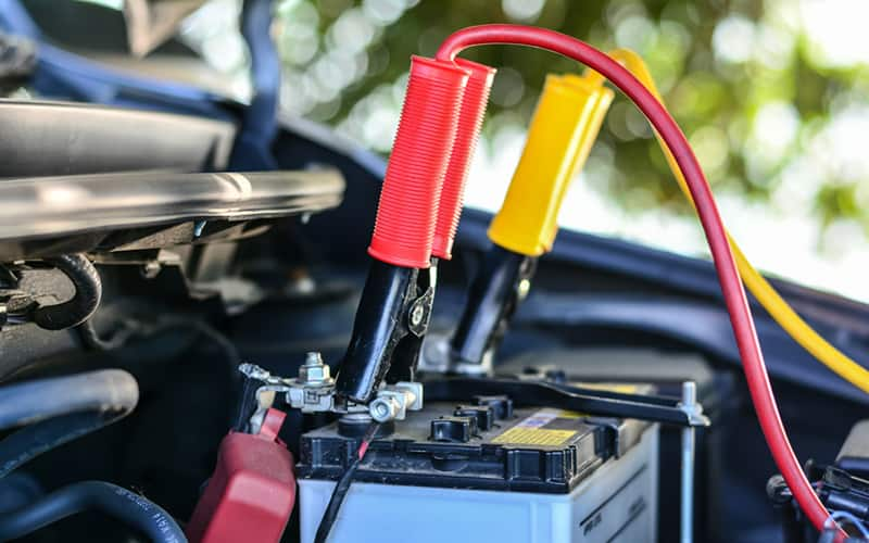 jumper cables connected to a car battery