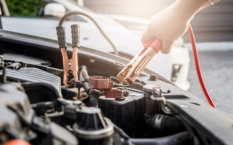 person's hand removing jumper cables from a car battery