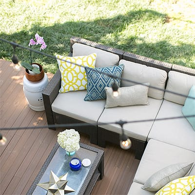 A deck decorated with outdoor patio furniture and string lights.
