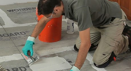 Man applying mortar using a square-notched trowel.