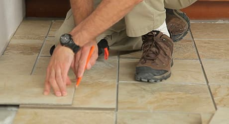 Man cutting directly over last tile.