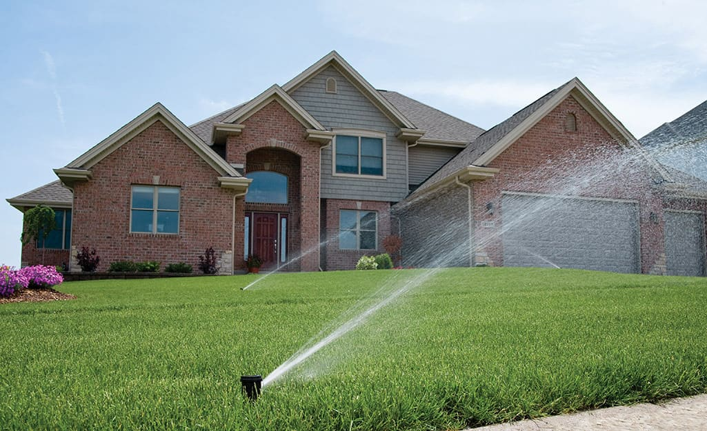 Sprinklers water a green lawn in front of a house.