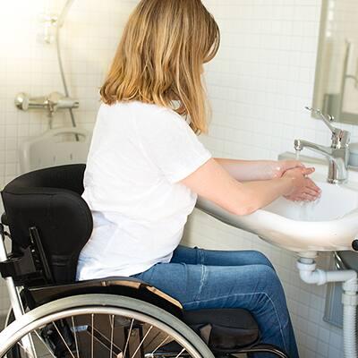 A person in a wheelchair washing their hands at a bathroom sink.