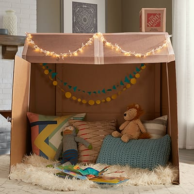 A completed and decorated box playhouse in a living room.