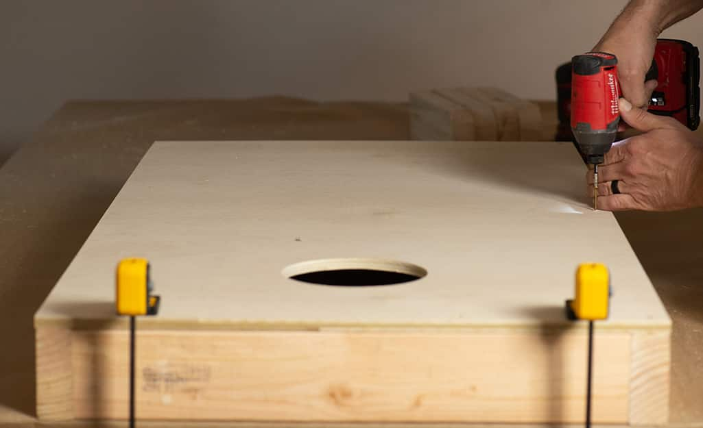 A person attaching the top of a cornhole board to its base.