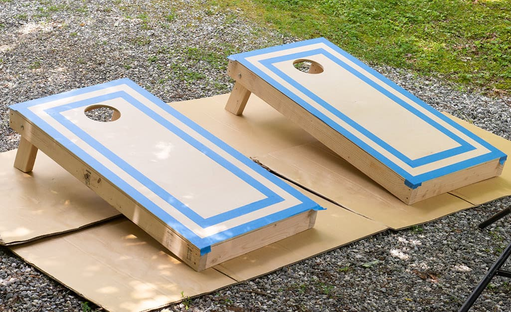 Taped off cornhole boards resting on cardboard waiting to be painted