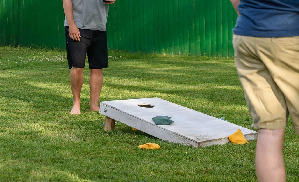 Two people playing cornhole on a lawn.