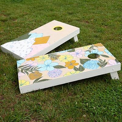 A cornhole target board sits on a lawn.