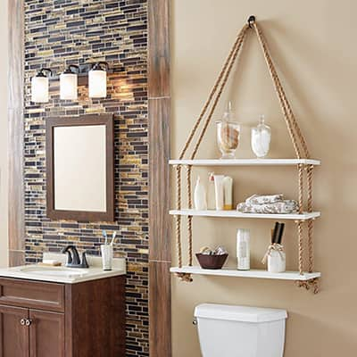 A DIY hanging rope shelf on the wall of a bathroom.