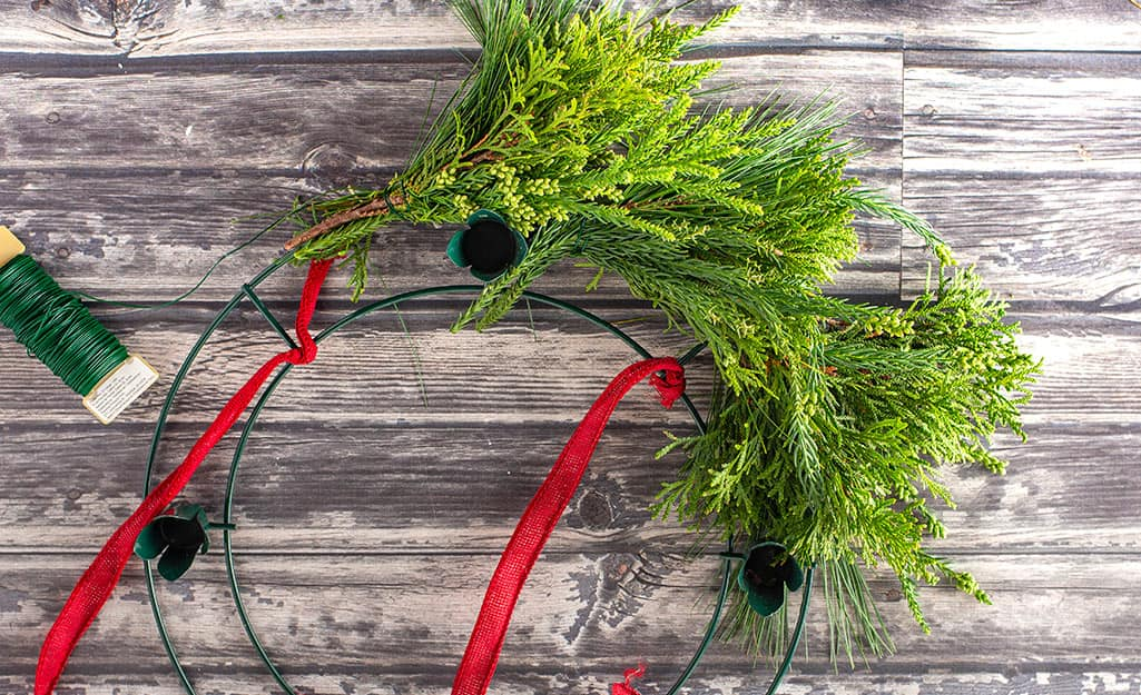 Several bundles of greenery tied to a wreath frame.
