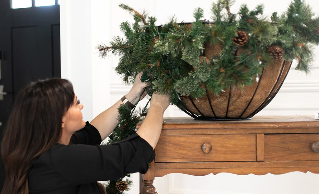 A woman begins attaching garland to a hanging planter.