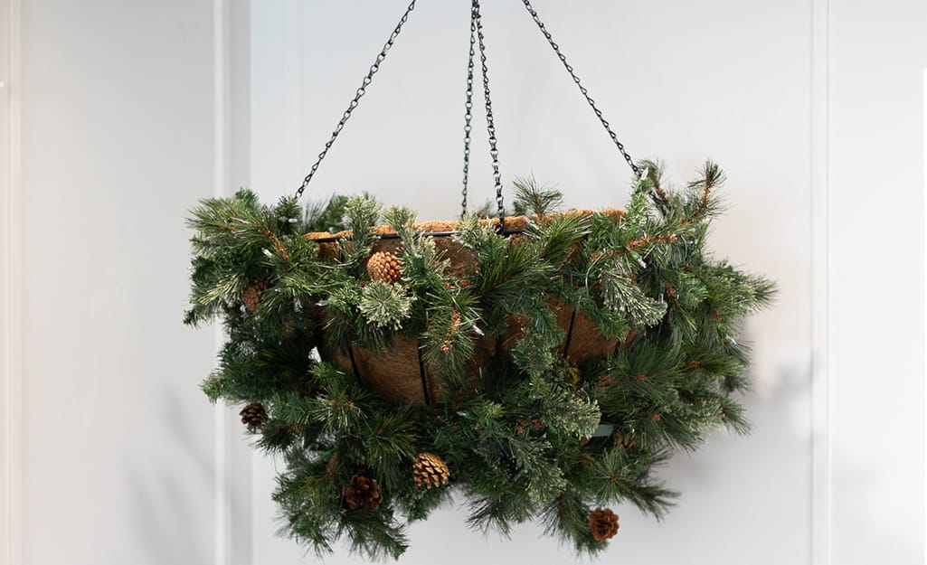 A planter wrapped in garland hangs in the corner of the room.