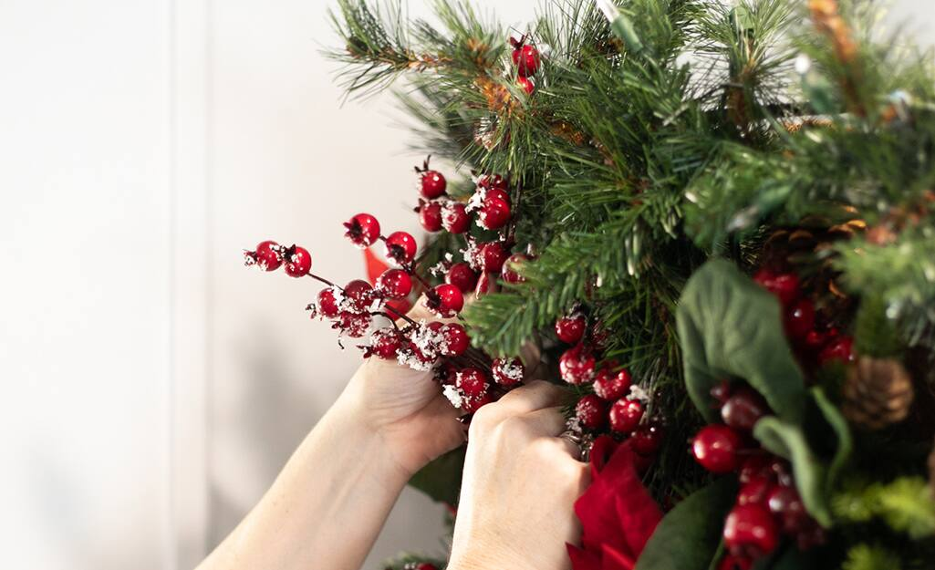 Holiday berry stems are added to garland.