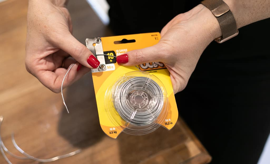 A woman uses a wire package with included cutting strip to cut wire.