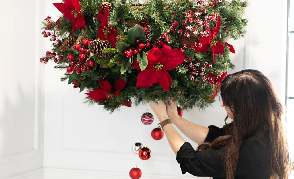 A woman hangs ornaments from a planter.