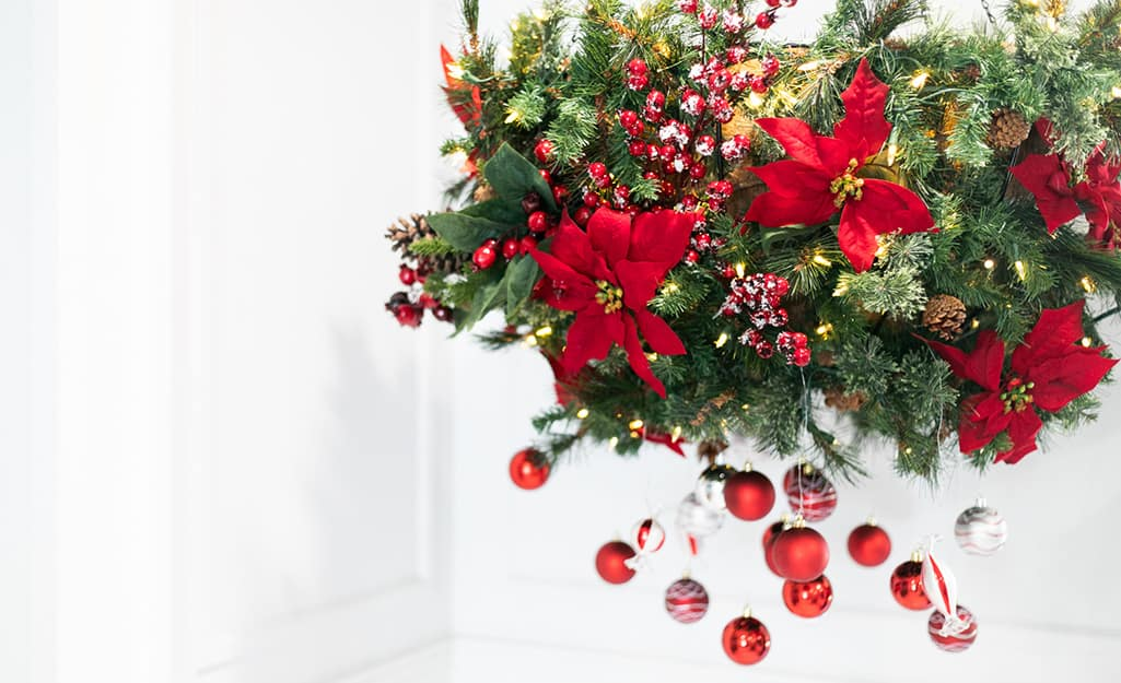 A finished hanging planter with garland, poinsettias, ornaments and berry stems.