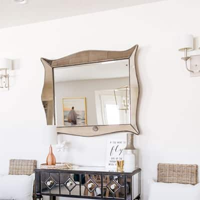 A large mirror hanging over a black and mirrored console table.
