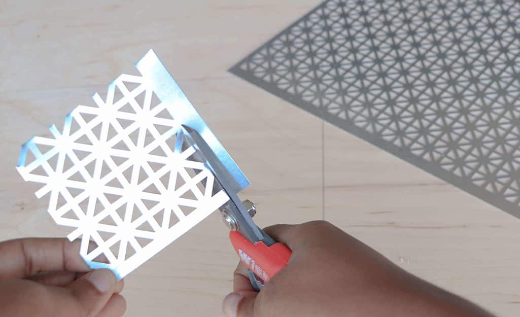 Metal snowflakes are cut out using snips.