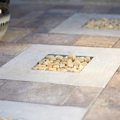 A concrete and pebble insert in a paver pathway.