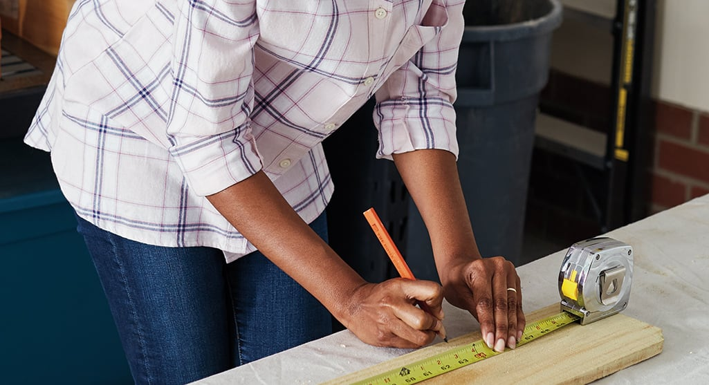 A person making measuring marks on a piece of wood.