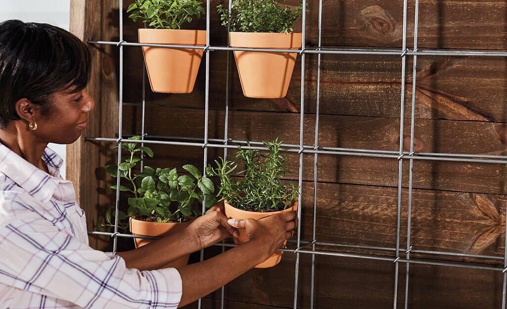 A person adding terra cotta pots onto a planter.
