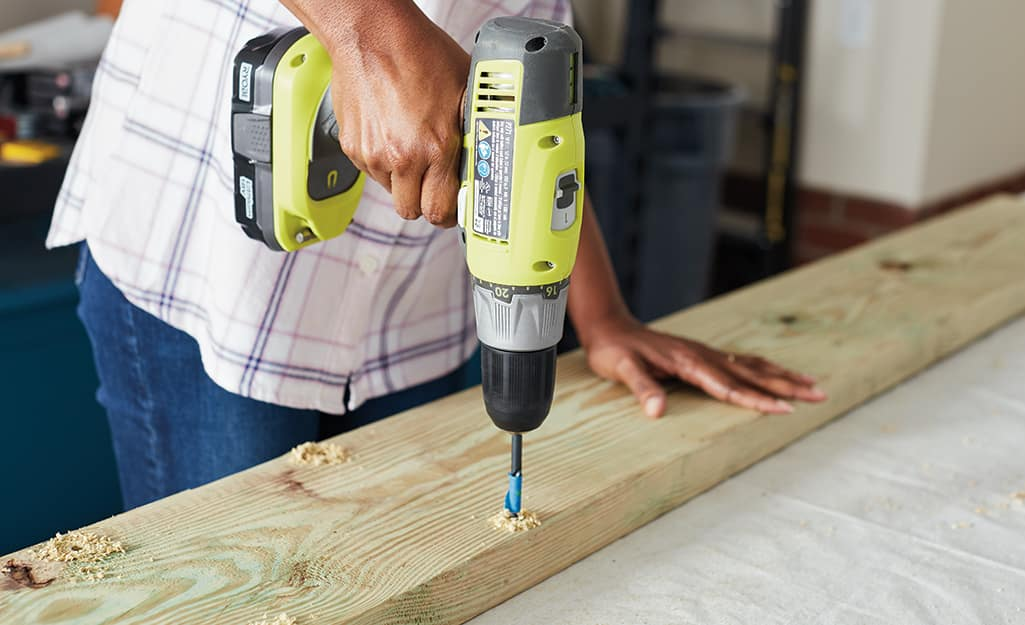 A person drilling a hole in a piece of wood.