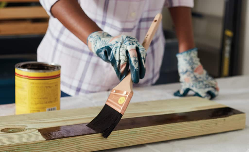 A person applying stain onto a piece of wood.