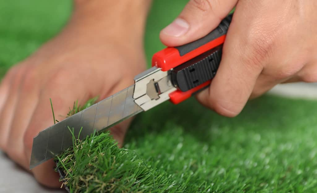 Someone cutting synthetic turf for a putting green with a utility knife.