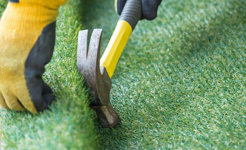 Someone using a hammer to nail down synthetic turf for a putting green.