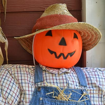 A homemade scarecrow sits on a front porch.