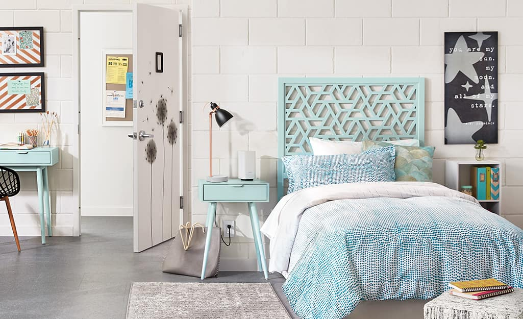A bed with a light blue headboard in a bedroom.