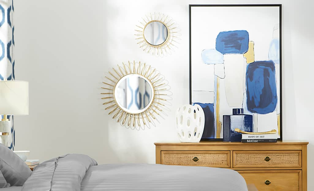 A bedroom with round mirrors and artwork on the wall.