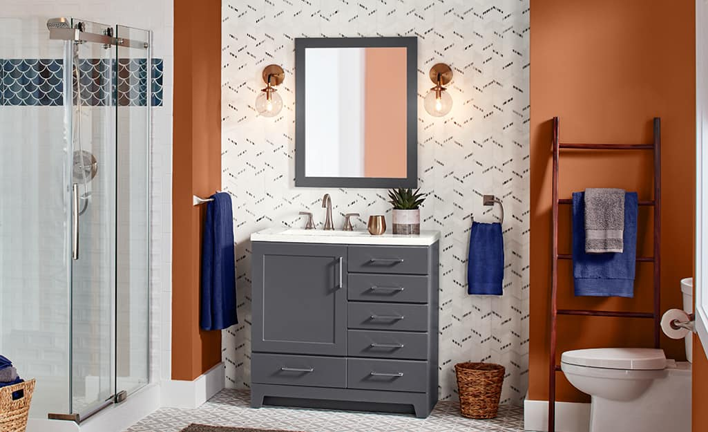 A bathroom with a grey vanity and clear shower doors.