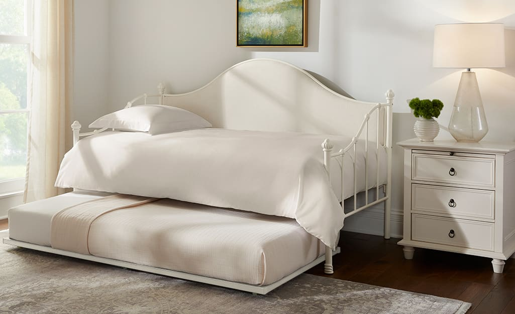 A white trundle bed in a bedroom.