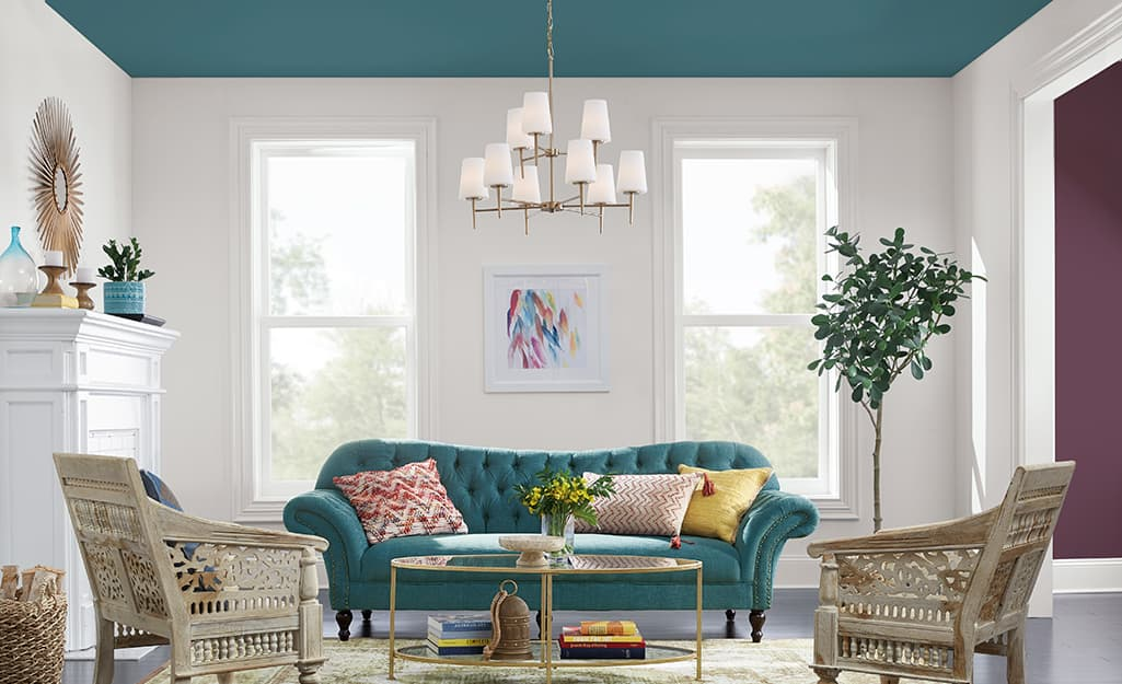 A living room with a blue sofa and a ceiling painted blue.