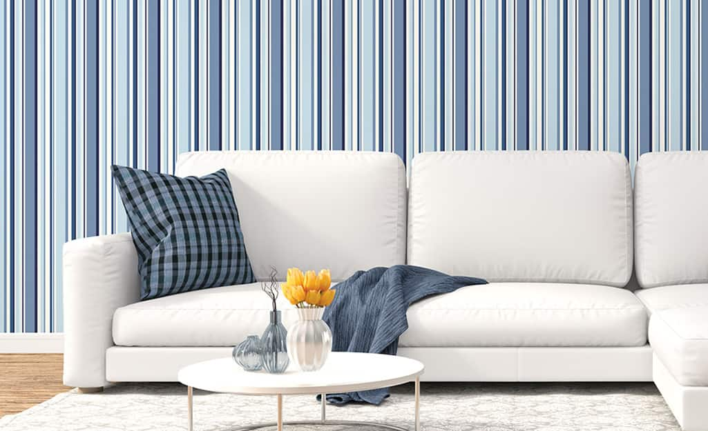 A living room with blue striped walls and a white sofa.