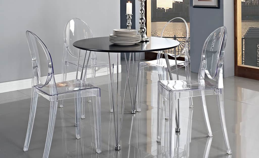 A dining set with clear, lucite chairs.