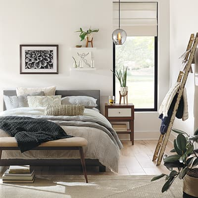 A bedroom with white walls and grey bedding.